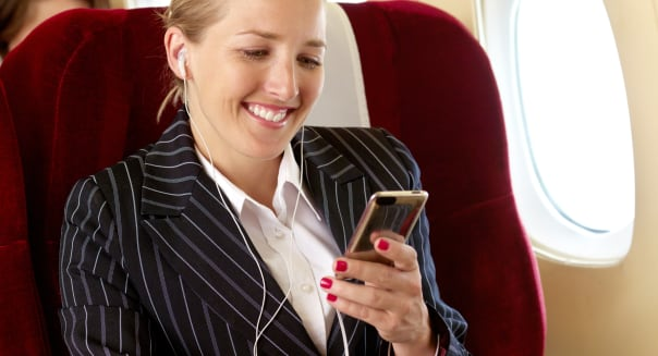 Woman listening to mp3 player in first class