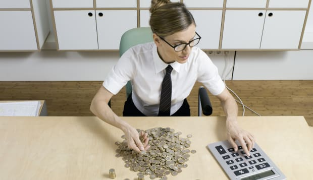 businesswoman counting money, using calculator