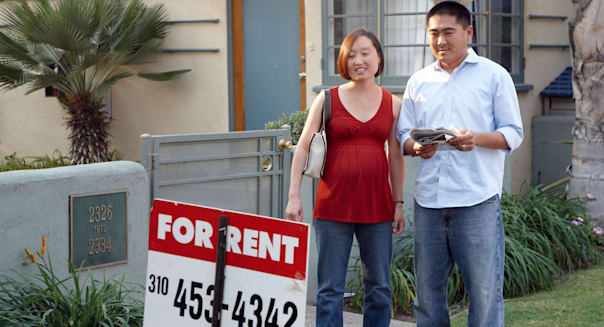 Pregnant Korean couple checks a sign for an apartment to rent