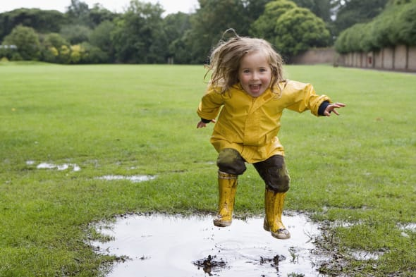 Girl (4-5) standing in puddle in park