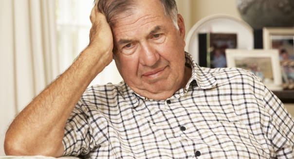 Unhappy Retired Senior Man Sitting On Sofa At Home