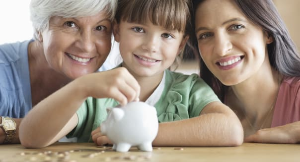 Three generations of women filling piggy bank