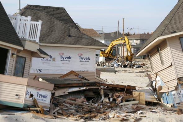 Superstorm Sandy Recovery (A crane, center, is seen at a distance as two damaged homes rest off their foundation as the cleanup