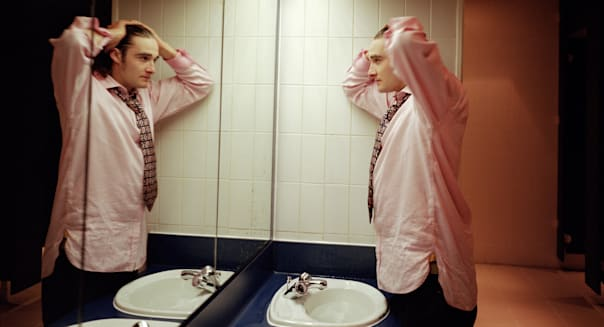 Young man looking in mirror in washroom