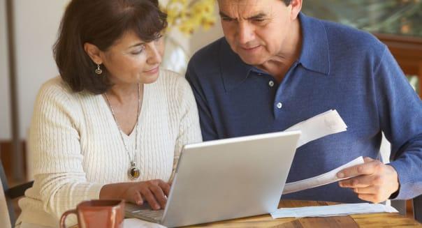 Senior Hispanic couple paying bills