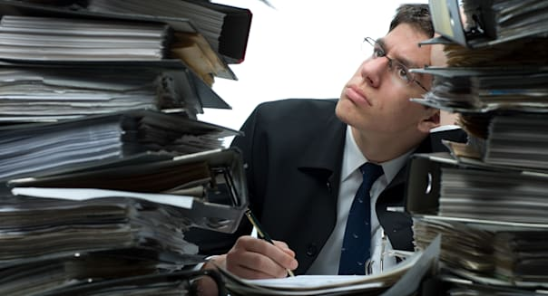 A confused man, holding a pen, sitting amidst piles of binders