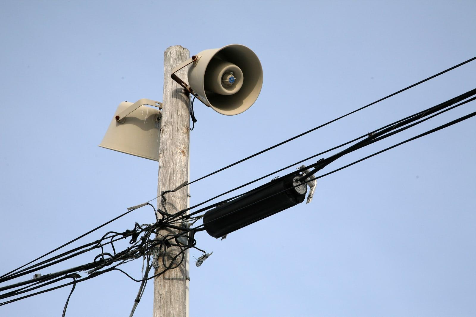 Warning sirens atop utility pole