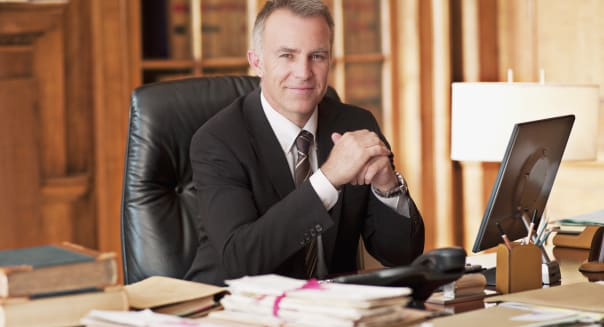 Smiling lawyer sitting at desk in office