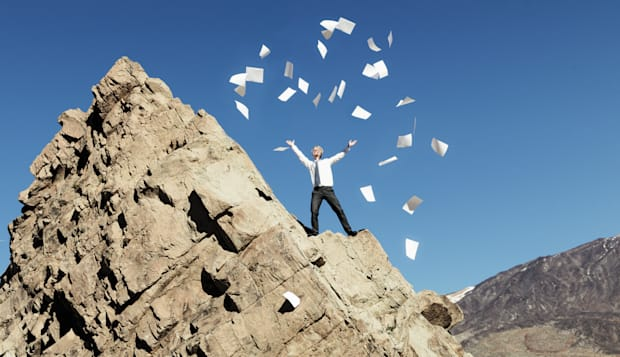 Businessman throwing paperwork from mountain top