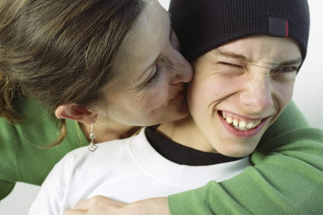 Mother kissing teenage boy (14-16) on cheek, close-up