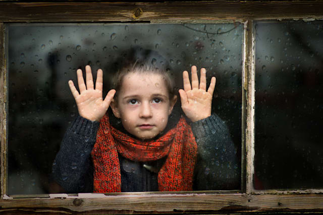 Little boy watching through the window