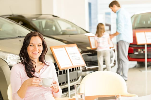 Female customer drinking coffee in car retail store
