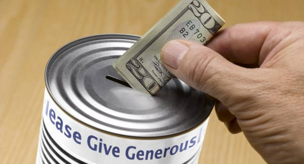 Person putting a twenty dollar bill into donation tin