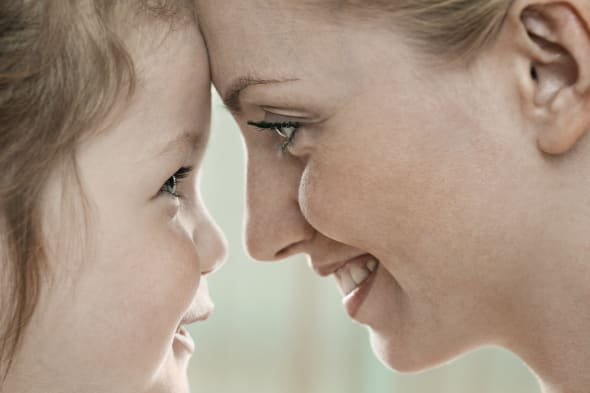 A smiling mother and daughter touching foreheads, close-up