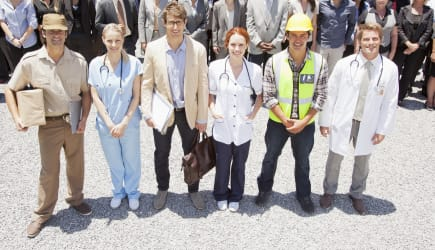 Portrait of smiling professionals and workers with business people in background