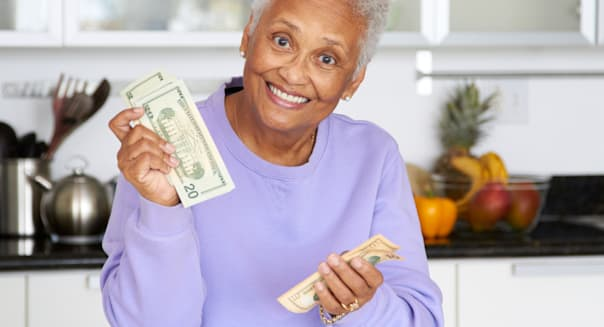 woman counting money in kitchen