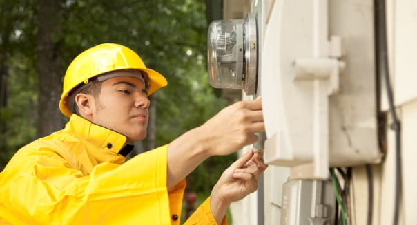 Electrician at outside electric meter on home