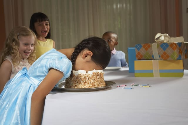 Four children laughing at girl, birthday cake, birthday party, presents, gifts