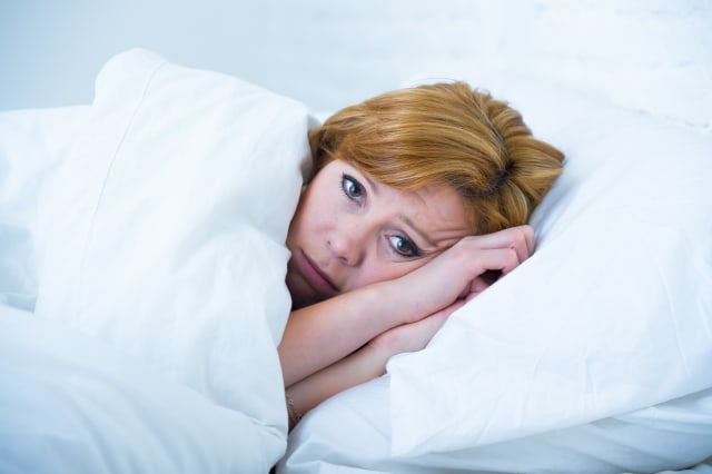 young attractive woman in sad and depressed face expression with eyes wide open lying in bed looking sick and unable to sleep su