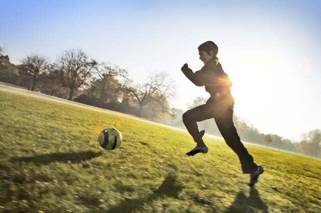 Young boy running in park with football