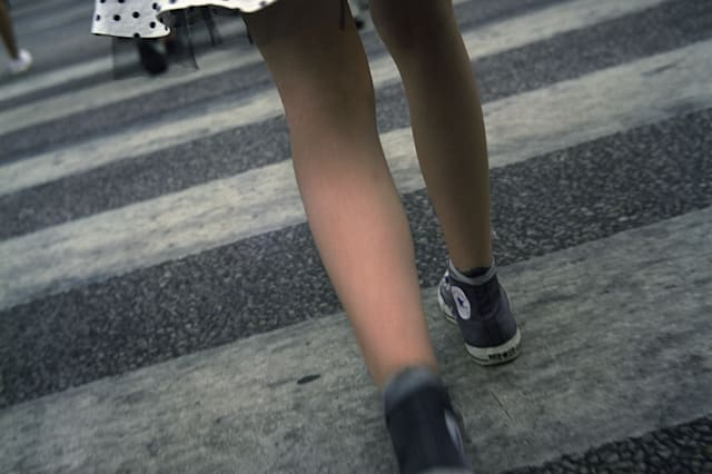 Low section view of a girl crossing the road