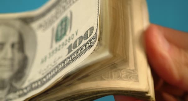 AM5279 thumbing a thick stack of American paper money $100 dollar bills.  cash; money; rich; wealthy; success; wad; lottery; gai