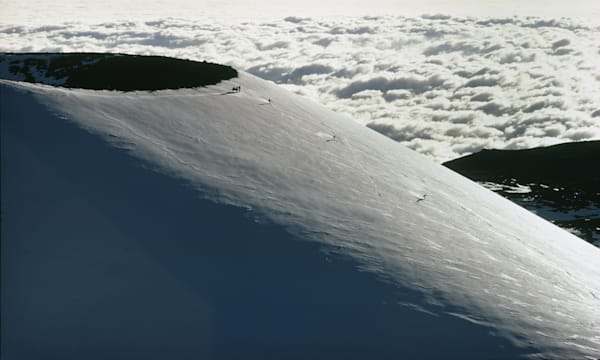 Mauna Kea, Hawaii. Skiers ski down the broad expanse of Mauna Kea in Hawaii.