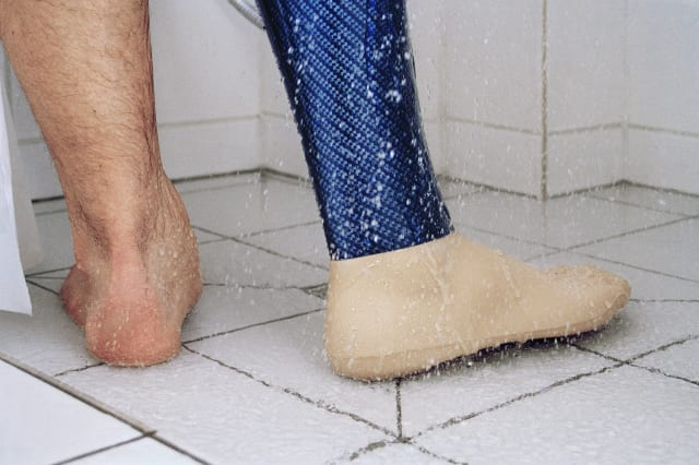 Low section of man showering with prosthetic leg