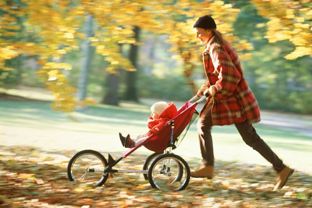 Mother pushing baby (12-15 months) in pushchair (blurred motion)