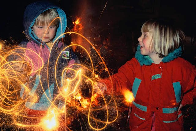 Two children (4-7) playing with sparklers at night