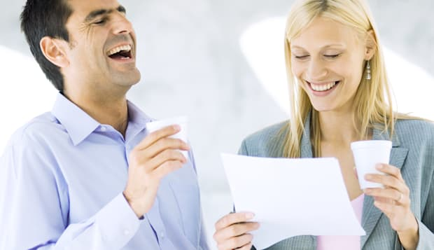 Businessman and businesswoman holding cups and laughing over document
