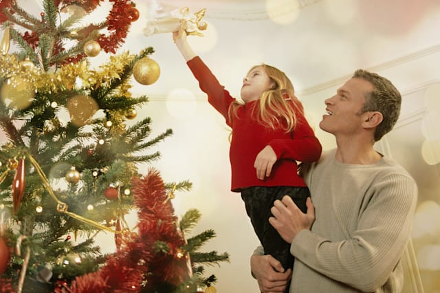 Father helping young daughter place star on top of Christmas tree