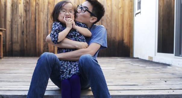 Father and daughter playfully hug and kiss