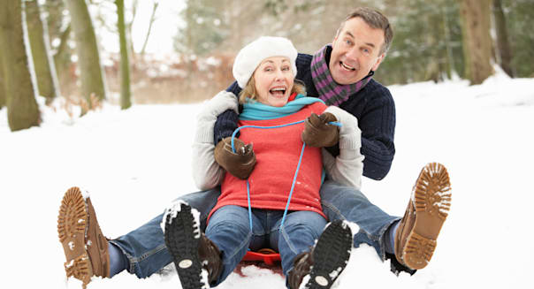 Senior Couple Sledging Through Snowy Woodland