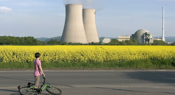 Young Boy with Bicycle Looking at Nuclear Power Station