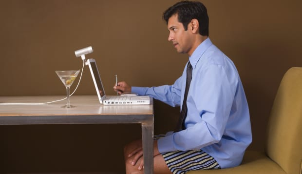 Businessman in boxer shorts with martini attending video conference