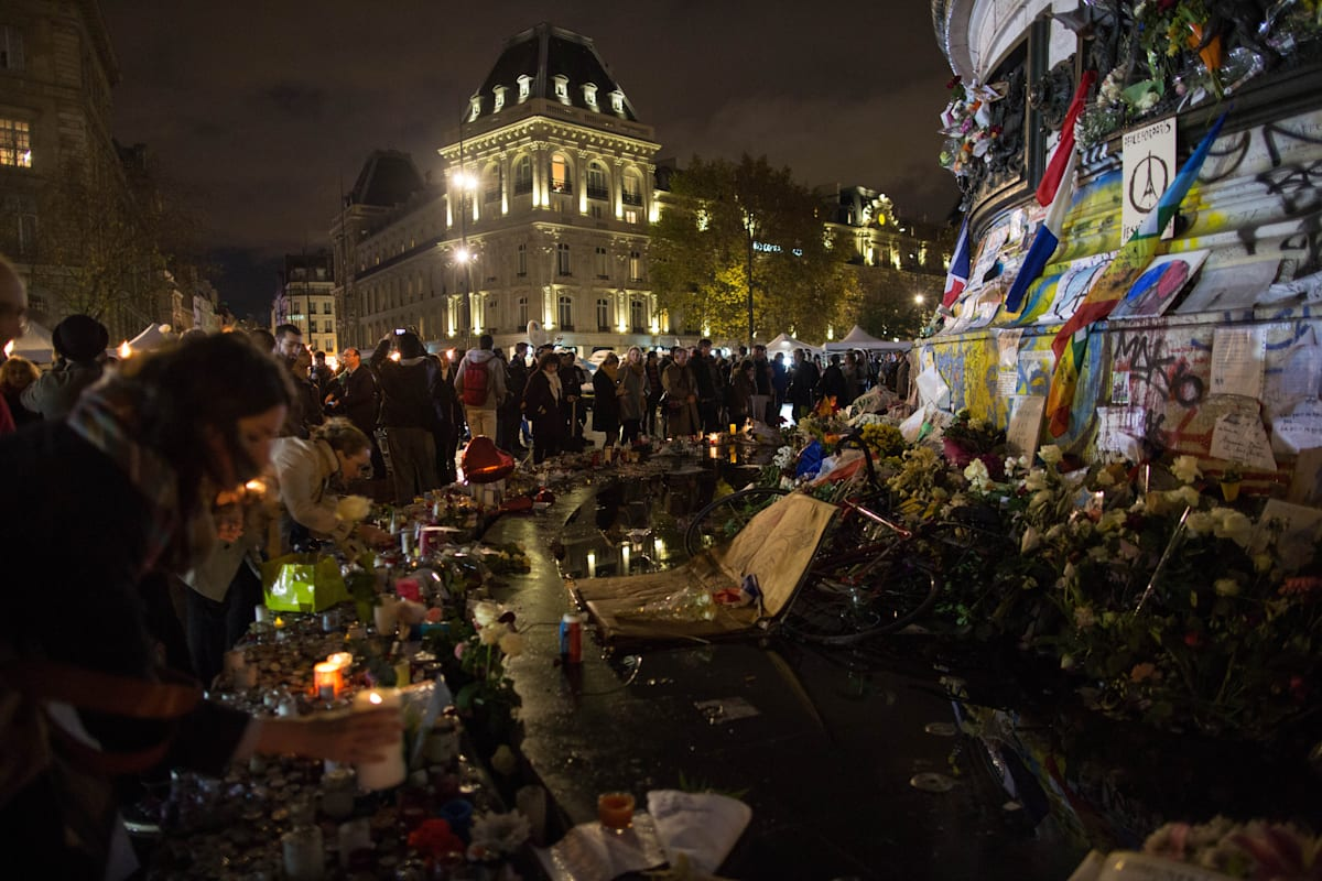 """People light candles at a makeshift memorial in front of """""""
