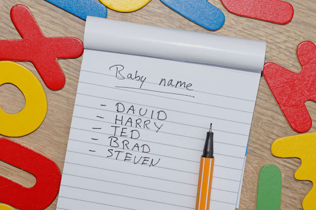 Choosing baby name for a boy written on a note, around wooden letters