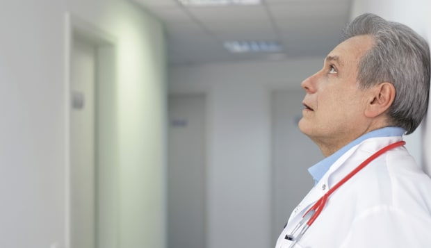 Gray-haired doctor with stethoscope around his neck standing in a hall, selective focus