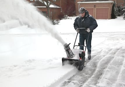 man working with a snow blowing ...