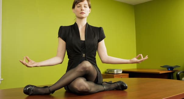 Businesswoman meditating on conference table