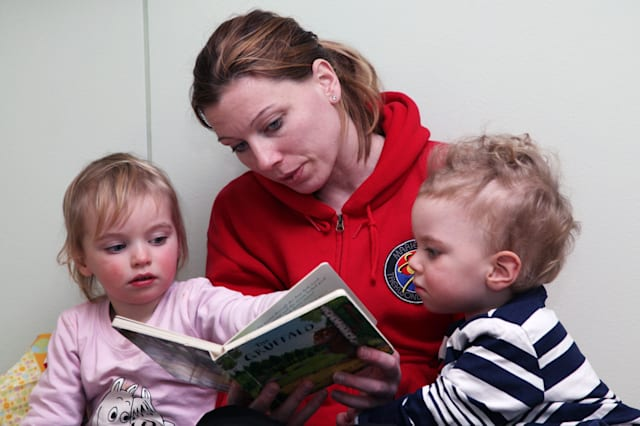 Mum mother reads reading to her children toddlers boy girl baby babies model released