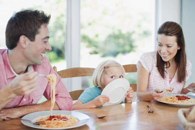 Parents watching daughter licking dinner plate
