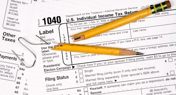 Tax forms a broken pencil and a twisted paper clip tell the story of a frustrated person