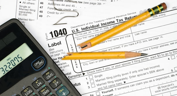 A tax form calculator broken pencil and bent paper clip shot the frustration of filing taxes