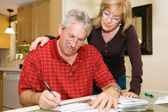 Mature couple in financial trouble is filling out a loan application