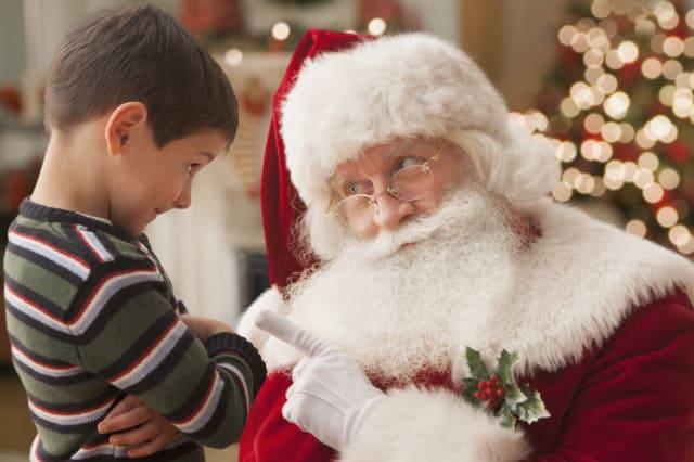 Santa lecturing Caucasian boy