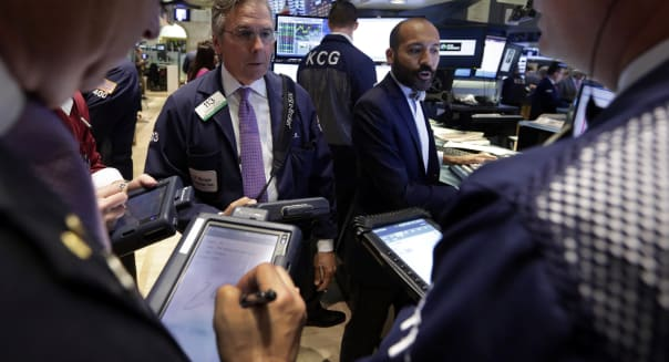 Specialist Fabian Caceres, background right, works with traders on the floor of the New York Stock Exchange Wednesday, July 31, 2013. Steady growth in the U.S. economy and higher company earnings are pushing the stock market higher in early trading. (AP Photo/Richard Drew)