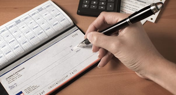 Writing a check to pay the bills with calculator and pen on desktop