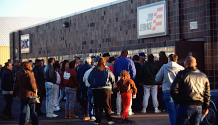Jobless people waiting in line outside unemployment office.